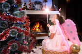 Little fairy girl with magic wand near a Christmas tree — Stock Photo