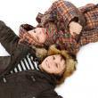 Two boys dressed in winter clothes lying on snow - Foto Stock