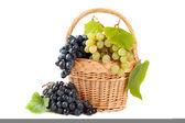 Uvas en la cesta con hojas de vid — Foto de Stock