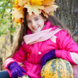 Girl in wreath of maple leaves with pumpkin in autumn park — Stock Photo #13747302
