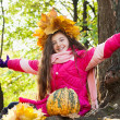 Girl in a wreath of maple leaves in autumn park — Stock Photo