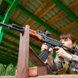 Young woman aiming at a target and shooting an automatic rifle f — Stockfoto