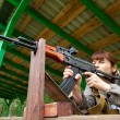 Young woman aiming at a target and shooting an automatic rifle f — Stock Photo