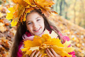 Girl in a wreath of maple leaves with autumn bouquet — Stock Photo