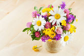 Vase with bouquet of flowers and healing herbs on wooden table — Stock Photo