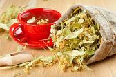 Xícara de chá de tília e flores em saco de lona na mesa de madeira — Foto Stock