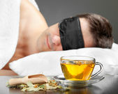 Man with Sleeping mask sleep on a bed, cup of herbal tea in the — Stock Photo