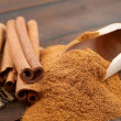 Cinnamon sticks and cinnamon powder in wooden scoop — Stock Photo #15411471