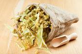 Fiori di tiglio in tela sacchetto sul tavolo di legno, medicina di erbe — Foto Stock