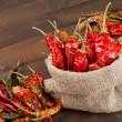 Red chili peppers in a canvas sack on wooden table — Stock Photo