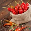 Stock Photo: Red chili peppers in a canvas sack on wooden table