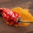 Red chili pepper and pile of ground chilly — Stock Photo