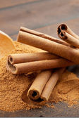 Cinnamon sticks and cinnamon powder in wooden scoop — Stock Photo