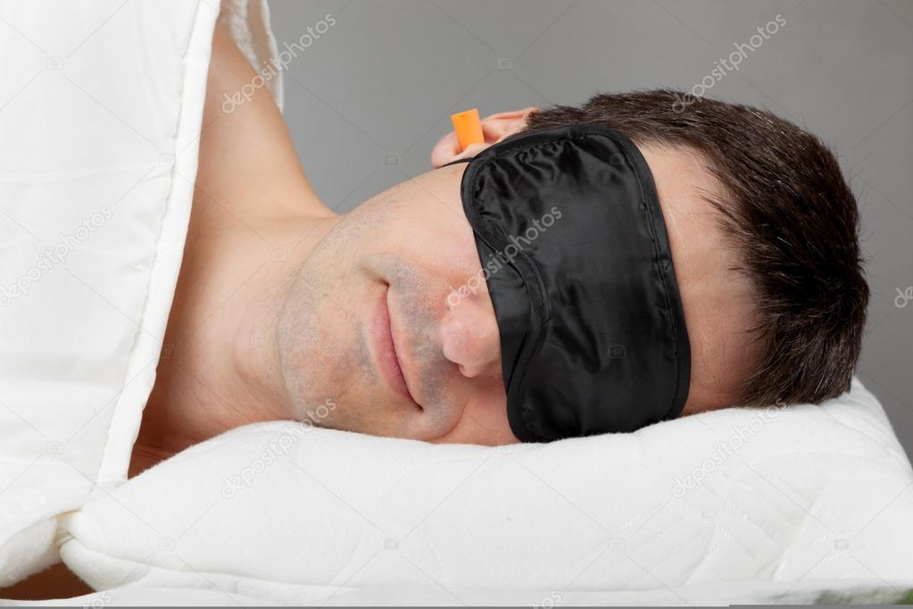 Man with Sleeping mask sleep and earplugs lying in bed — Stock Photo #15736193
