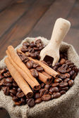 Sack with coffee beans and cinnamon, wooden scoop — Stock Photo