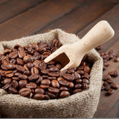 Sack with coffee beans and wooden scoop — Stock Photo