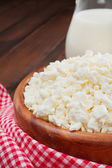 Cottage cheese in rustic wooden plate — Stock Photo