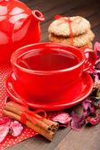Wakacje herbaty w czerwony kubek, ciasteczka, czajnik i cynamonu na k — Zdjęcie stockowe