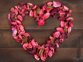 Flower Petals forming a heart shape against wooden background — Stock Photo