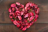 Ahşap arka plan kalp şekli oluşturan çiçek yaprakları — Stok fotoğraf