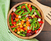 Mixed vegetables in wooden bowl on kitchen table — Stock Photo