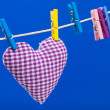 Single heart on clothesline with clothespins, blue background — Stock Photo