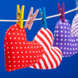 Hearts hanging on a clothesline with clothespins, focus on red. — Stock Photo