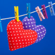 Two hearts hanging on a clothesline with clothespins, blue background - Stock Photo