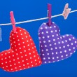 Hearts hanging on a clothesline with clothespins, blue background — Stock Photo