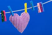 único coração no varal com prendedores de roupa, fundo azul — Foto Stock