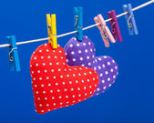 Two hearts hanging on a clothesline with clothespins, blue background — Stock Photo