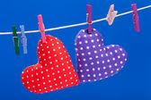 Corazones colgando de una soga con el fondo de pinzas para la ropa, azul — Foto de Stock