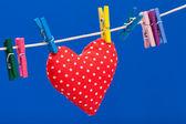 červené srdce visí na prádelní šňůře s kolíčky na prádlo, modré pozadí — Stockfoto