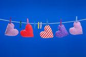 Corazones colgando en un tendedero con pinzas para la ropa, azul backgroun — Foto de Stock