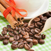 Coffee cup, cinnamon sticks and coffee beans on kitchen table — Stock Photo