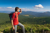 Man stands on a peak of mountains and looking the scenery — Stock Photo