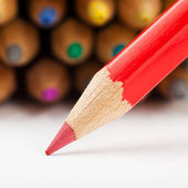 Red pencil draws or writing on paper sheet, colored pencils as b — Stock Photo
