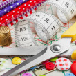 Sewing items: buttons, colorful fabrics, scissors, measuring tap — Stock Photo