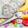 Sewing items: buttons, scissors, measuring tape  on sewing patte — Stock Photo