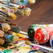 Art brushes, oil paint tubes, artist palette on wooden table — Stock Photo