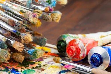 Art brushes, oil paint tubes, artist palette on wooden table
