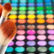 Makeup brushes and set of colorful eye shadows as background — Stock Photo