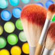 Makeup brushes and set of colorful eye shadows as background - Stock Photo