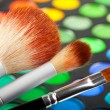 Makeup brushes and set of colorful eye shadows - Stock Photo