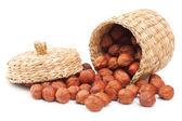 Hazelnuts and basket on white — Stock Photo