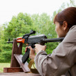 Young woman shooting an automatic rifle for strikeball - Stock Photo