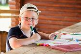 Cute boy drawing in wooden gazebo outdoors — Stock Photo