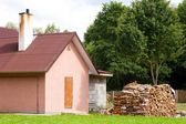 Small house with firewood outside — Stock Photo