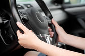 Woman hands holding steering wheel in luxury car — Stock Photo