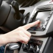 Finger on dashboard with gps panel and tv, dvd, audio system — Stock Photo